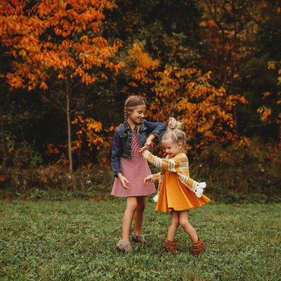 sisters dancing on autumn grass